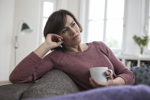 Woman at home sitting on the sofa with cup - RBF05393