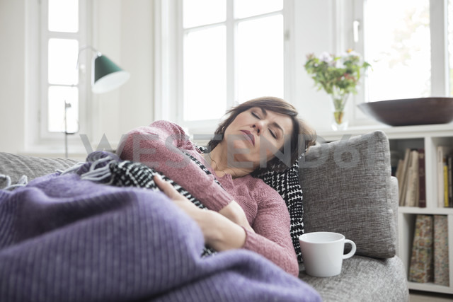 Woman with stomach ache lying on the sofa - RBF05396 - Rainer Berg/Westend61