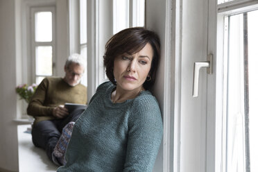 Disappointed woman with man in background - RBF05411