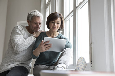 Couple sharing tablet at the window - RBF05417