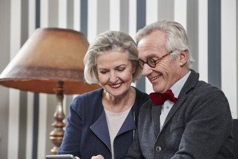 Happy senior couple using smartphone at home - RHF01683