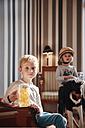 Boy holding fruit gum beer mug and sister on rocking horse - RHF01686