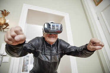 Senior man in motorcycle suit wearing VR glasses - RHF01704