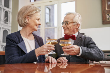 Smiling senior couple clinking champagne glasses - RHF01716