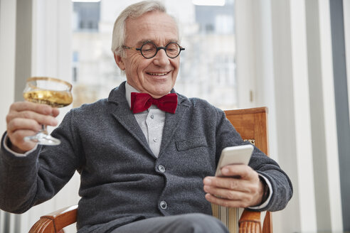 Smiling senior man with cell phone sitting on chair holding champagne glass - RHF01725