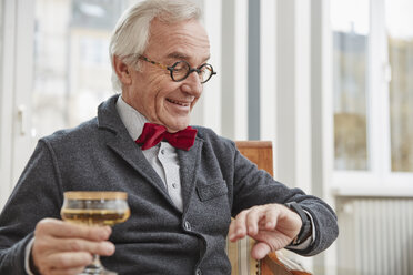 Smiling senior man sitting on chair holding champagne glass looking on smartwatch - RHF01728