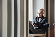 Senior man sitting in windowsill reading magazine - RHF01743