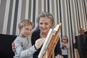 Grandmother and grandson with Dali moustache at easel - RHF01761