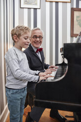 Grandfather and grandson playing piano together - RHF01764