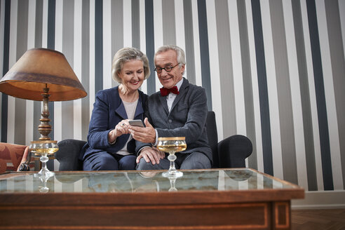 Happy senior couple sitting on couch with smartphone - RHF01773