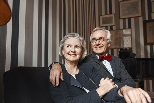 Happy senior couple sitting on couch - RHF01776