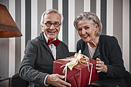 Happy senior couple sitting on couch with gift - RHF01779