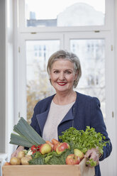 Portrait of smiling senior woman holding box with produce - RHF01791