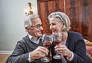 Smiling senior couple clinking red wine glasses - RHF01797