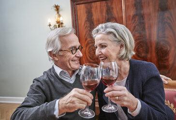 Smiling senior couple clinking red wine glasses - RHF01797