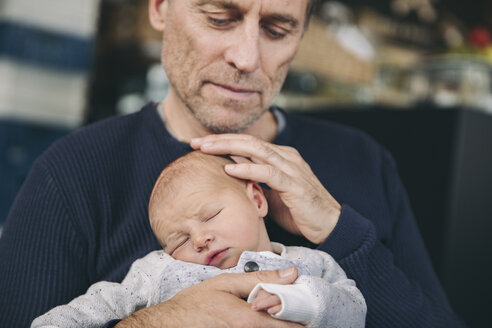 Mature father touching the head of his sleeping baby - MFF03416