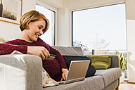 Smiling pregnant woman on couch shopping online - UUF09587