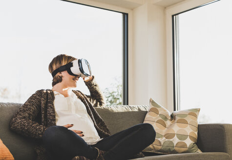 Pregnant woman on couch wearing VR glasses - UUF09602