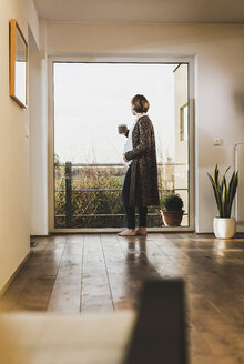 Pregnant woman standing at the window holding a mug - UUF09614