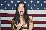 Young woman standing in front of US flag, making naughty hand sign - KKAF00219