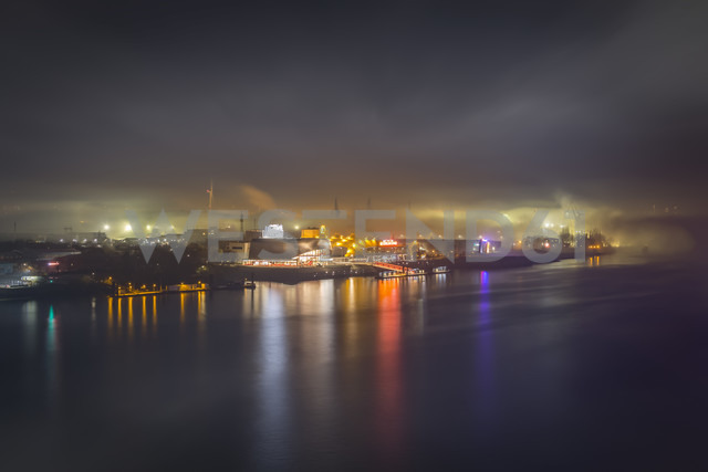 Germany, Hamburg, view to the harbor with lighted musical theater in the fog at night - NKF00470