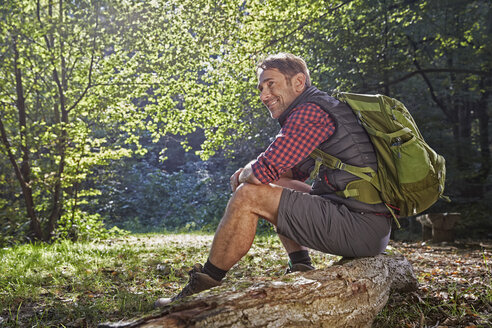 Hiker in forest sitting on tree trunk - FMKF03324