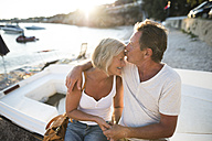 Senior couple sitting on edge of a boat on the beach at evening twilight - HAPF01260