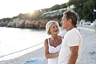 Senior couple relaxing on the beach at evening twilight - HAPF01263