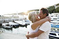 Happy senior couple on quai hugging at evening twilight - HAPF01266