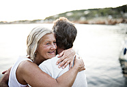 Happy senior woman hugging her husband in front of the sea - HAPF01275