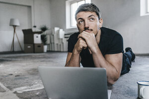 Man lying on floor with laptop in empty loft - KNSF00840