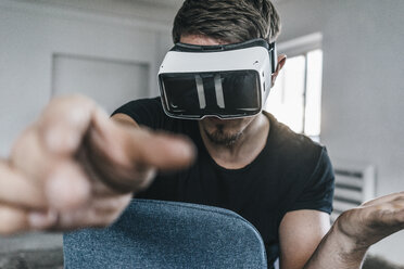 Man sitting on chair wearing VR glasses - KNSF00843
