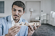 Portrait of confident businessman holding architectural model - KNSF00852