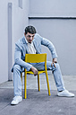 Portrait of confident businessman sitting on yellow chair - KNSF00870