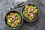 Two bowls of avocado salad with rocket, pomegranate seed, kaki, feta and walnuts - SARF03100