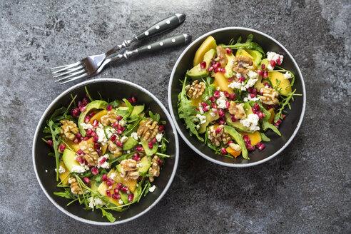 Two bowls of avocado salad with rocket, pomegranate seed, kaki, feta and walnuts - SARF03100