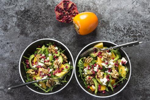 Two bowls of avocado salad with rocket, pomegranate seed, kaki, feta and walnuts - SARF03103