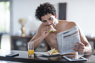 Young man at home reading newspaper and eating sandwich - ZEF12027