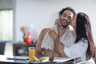 Young woman kissing boyfriend at home during breakfast - ZEF12030