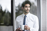 Businessman with cup of coffee looking out of window - ZEF12033