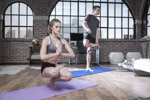 Young man and woman doing yoga exercise in studio - ZEF12046