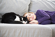 Portrait of little girl lying on couch with cat - LVF05773