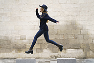 Young woman jumping from bollard to bollard - KKAF00228