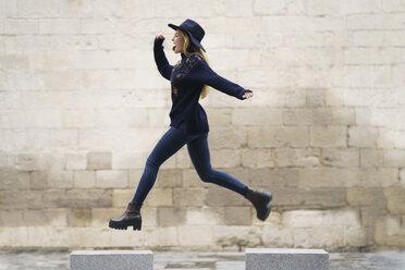 Young woman jumping from bollard to bollard - KKAF00228