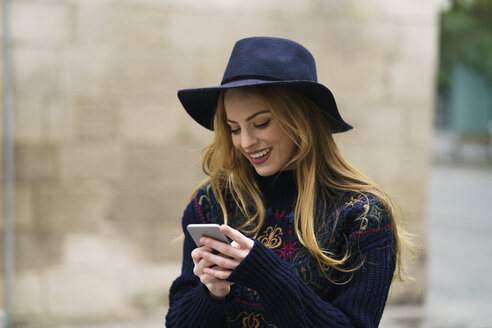 Smiling young woman looking at cell phone - KKAF00231