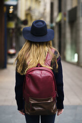 Back view of tourist with blue hat red backpack - KKAF00234