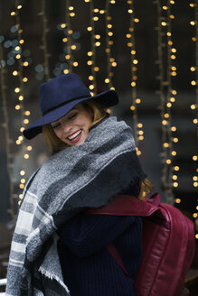 Portrait of laughing young woman wearing blue hat and scarf - KKAF00237
