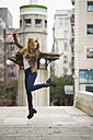 Excited young woman jumping in the air - KKAF00243