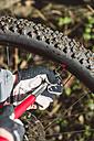 Man inflating tire of his mountain bike - RAEF01625