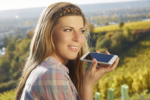 Young woman in a vineyard using cell phone - FMKF03366